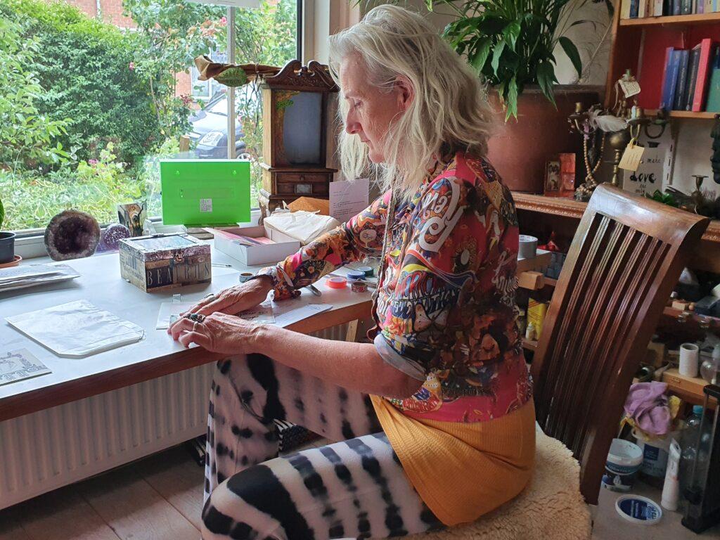 Beatrijs zit in haar atelier en werkt. Het is een woonkamer met veel kleuren en bedrijvigheid. Beatrijs is geconcentreerd op een envelop die ze verstuurt voor haar maandelijkse abonnement.