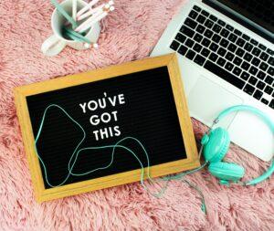 """Een krijtbord met de tekst """"you've got this"""" naast een laptop en torkooise koptelefoon."""